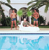 Two young men fanning senior woman with palm fronds by pool, portrait